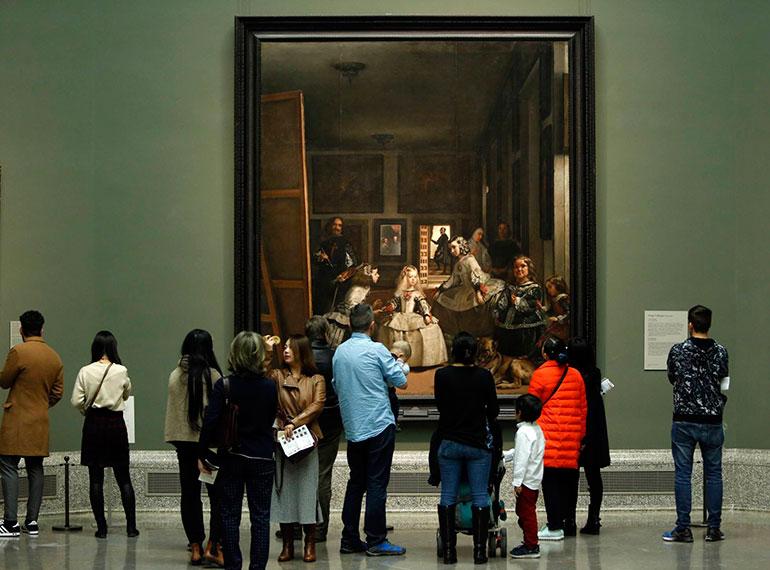 Visitantes observandoel cuadro de las Meninas de Velazquez en el Museo Nacional del Prado.